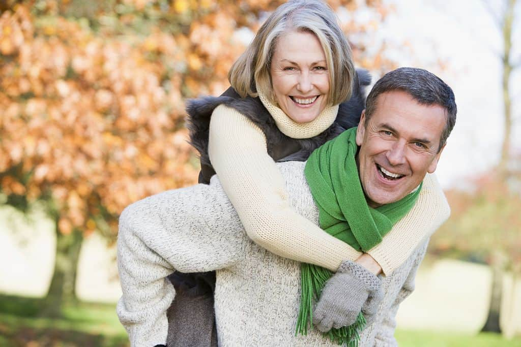 middle aged man giving woman piggyback ride - happy life hacks