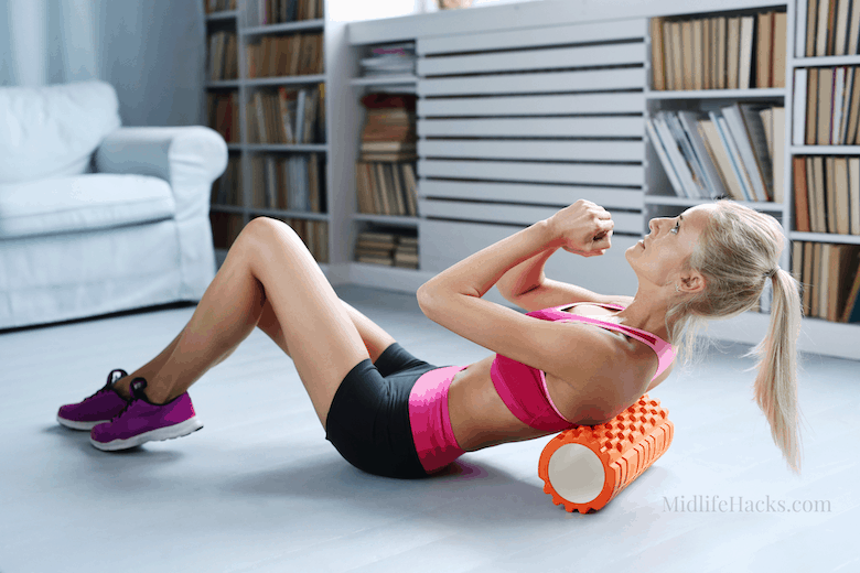 Woman in living room with foam roller massager for a self-massage tool workout