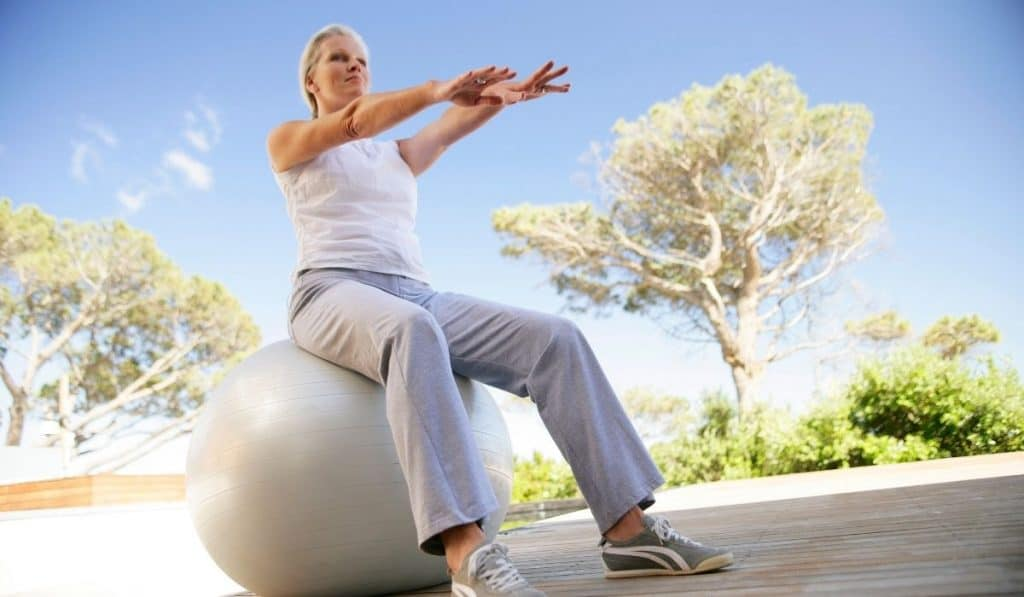 middle aged lady outside using exercise ball for stability