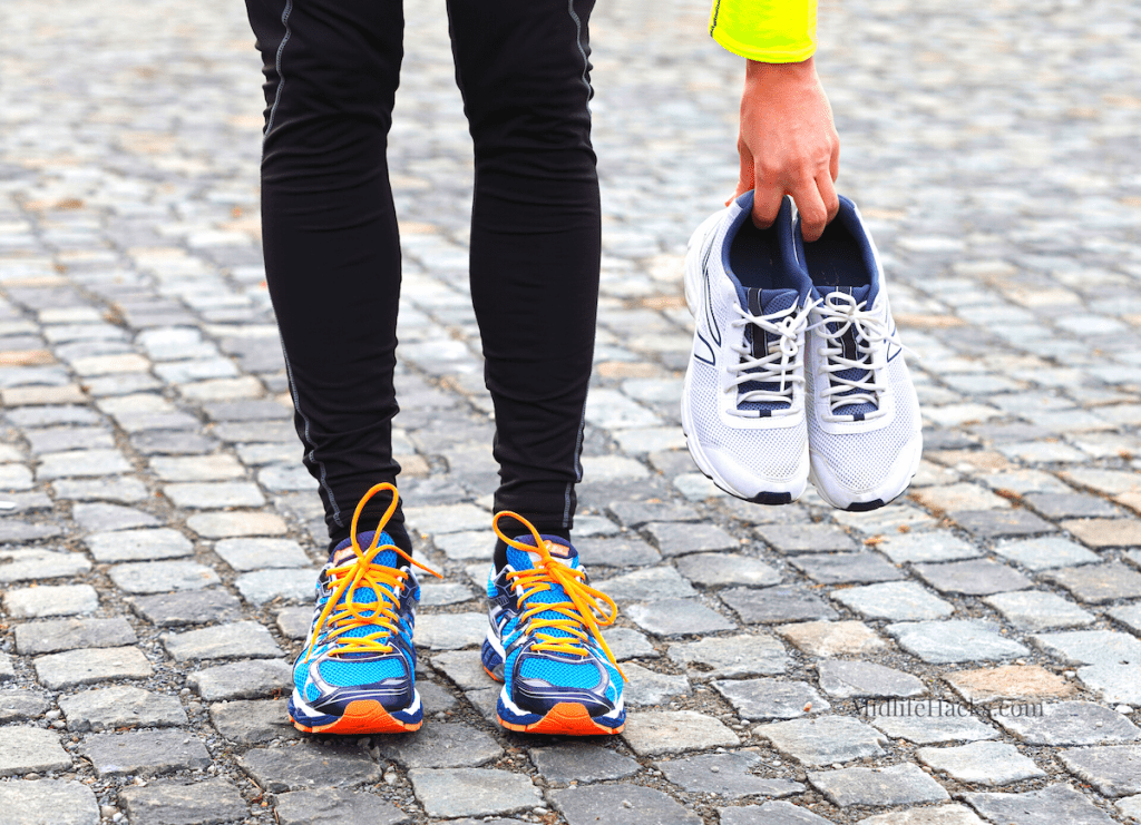 Lower legs wearing running shoes and hand holding a pair