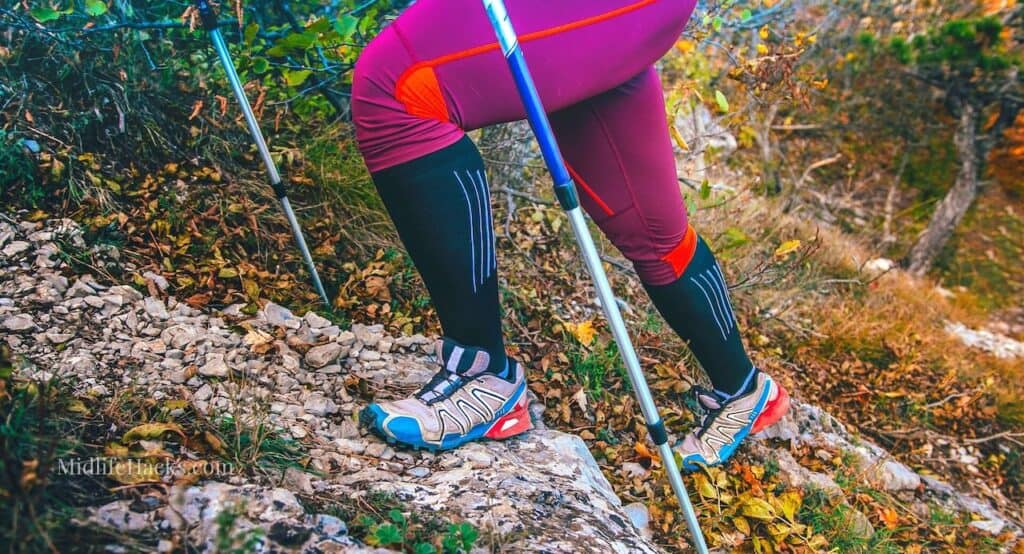 The legs in tights and shoes of a heavyweight female walker with poles across an uneven but lovely terrain