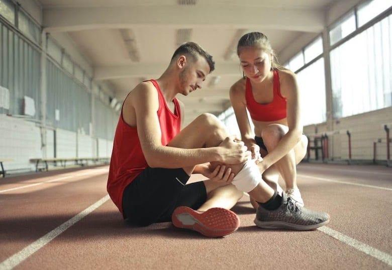 Girl tending to man suffering from lower leg pain