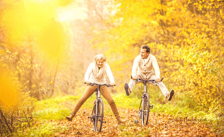 Mature couple cycling through wood in the fall