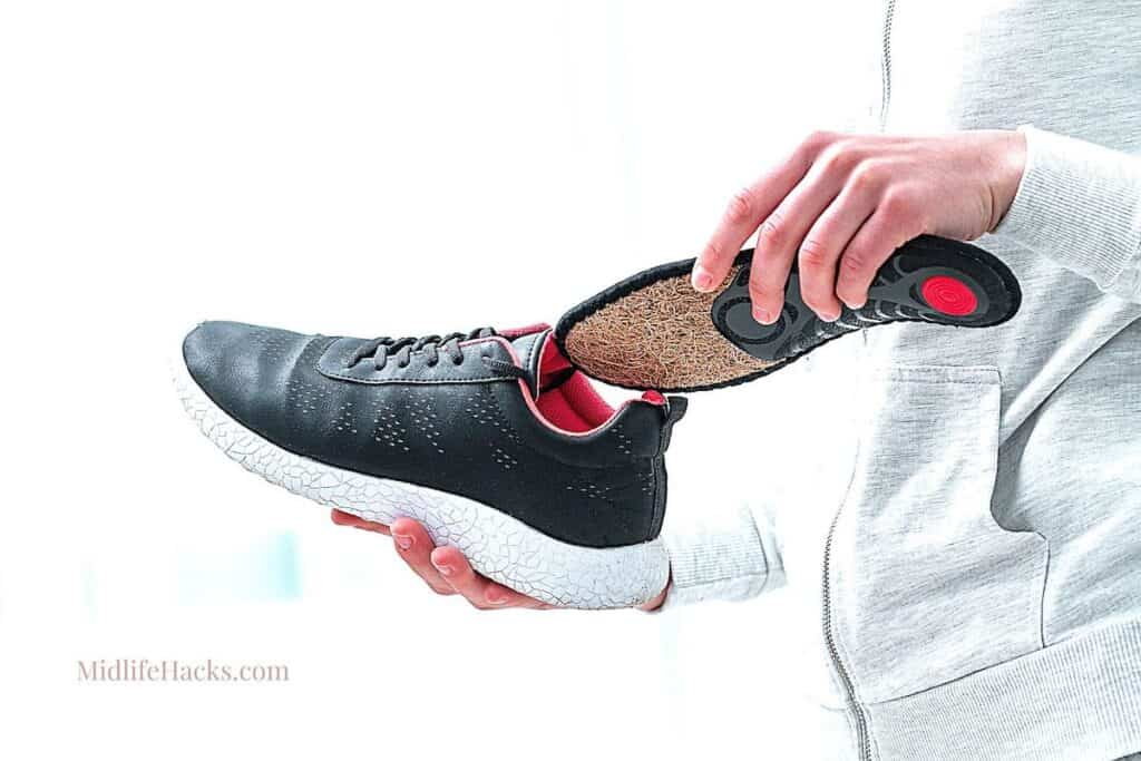 A hand slipping an orthotic sole into a sports shoe