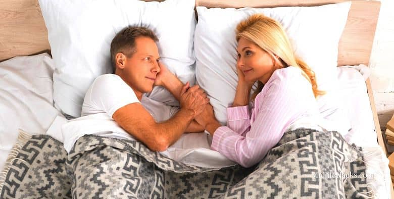 Mature couple in bed looking at each other and holding hands - sex is good for anyone losing weight after 50
