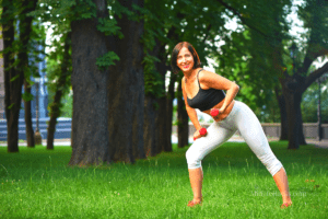 Middle aged attractive woman with toned muscles exercising in park with light weights