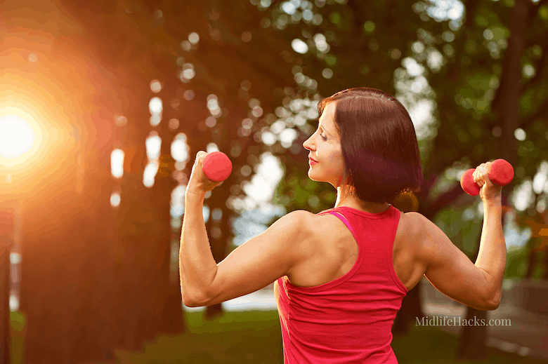 Mature woman head & shoulder with weights in park