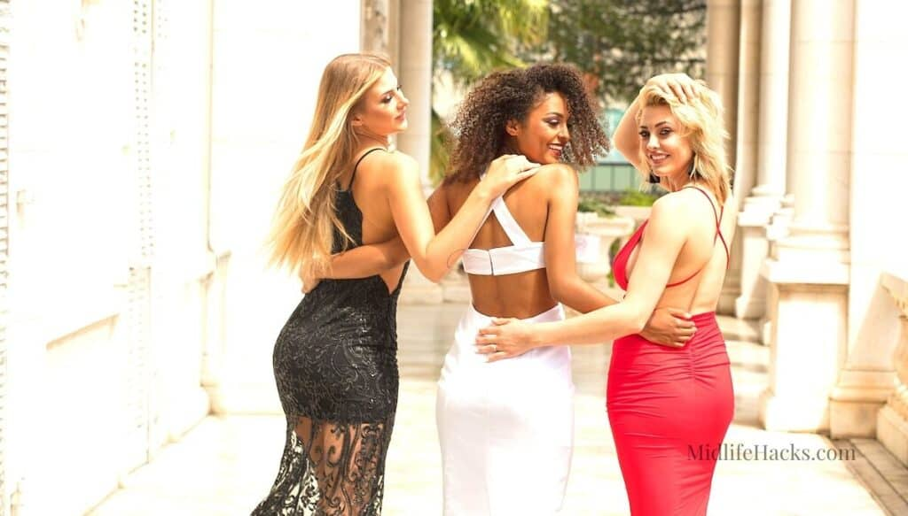 3 ladies in their finest outfits with backless dresses walking down a stately home palisade