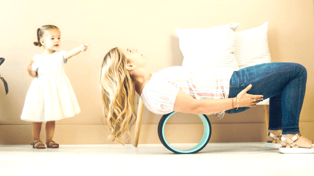 Woman in front room using the Chirp Wheel with a diagrammatic spinal overlay