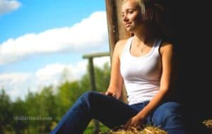 Girl sitting in the countryside wearing tank top