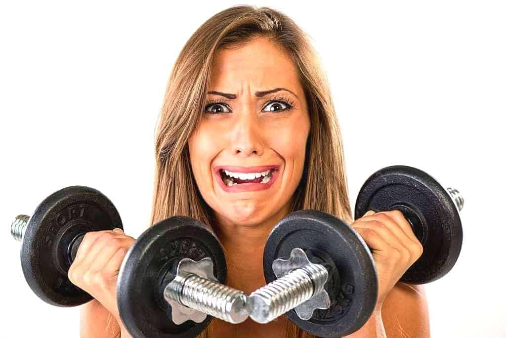 Stressed woman training with a set of dumbbells
