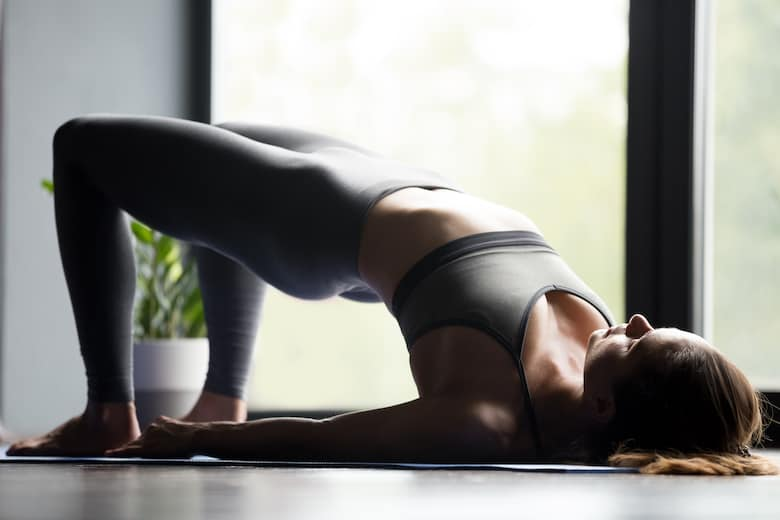 Young sporty woman doing Glute Bridge exercise to strengthen her core
