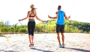 man and woman jump rope outside with their backs to us wearing the best shoes for jumping rope