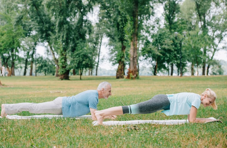 mature couple doing a plank outdoors