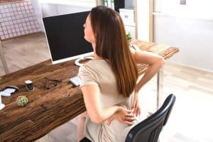 Woman at keyboard with a knots in her back