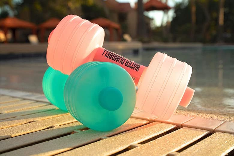 2 water-filled dumbbells by a pool