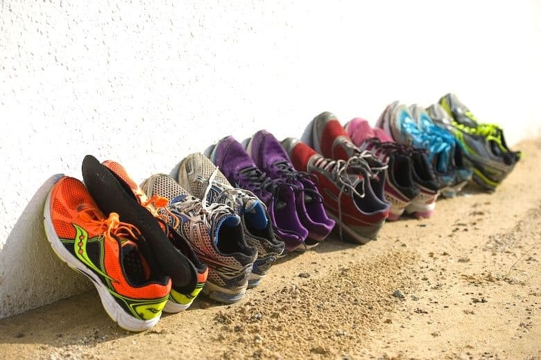 running shoes to be recycled lined up beside a wall