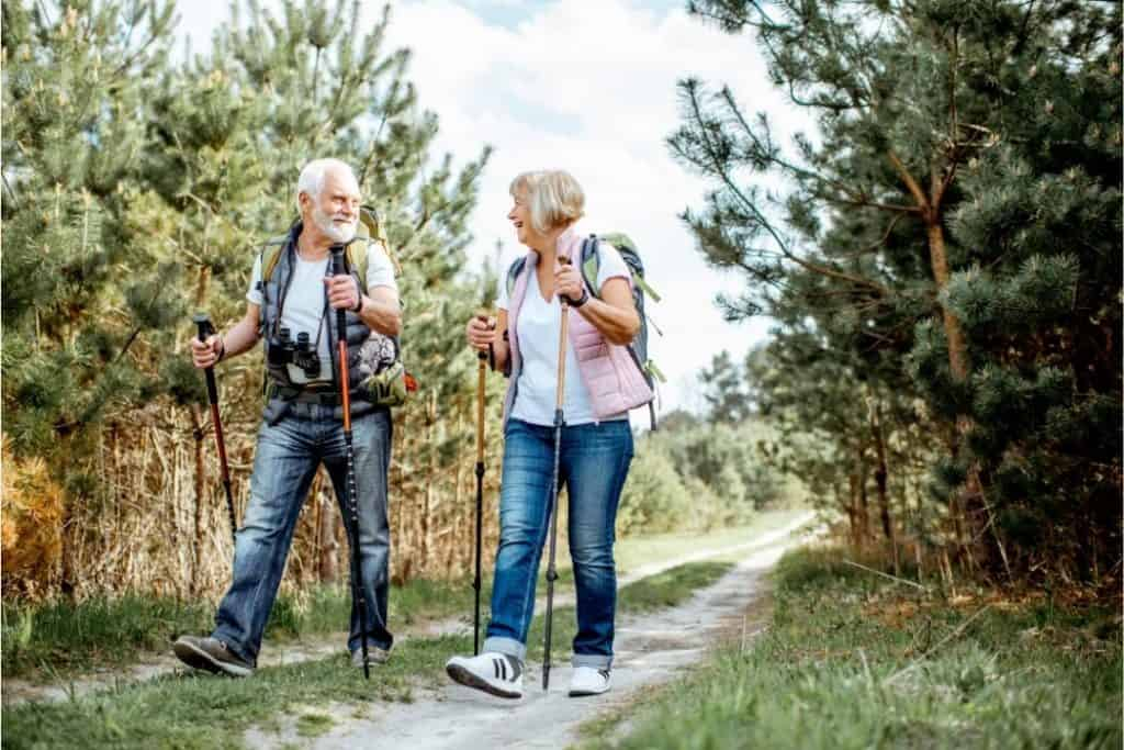 Midlife couple pursuing the health benefits of walking with poles along a track in the conifer forest
