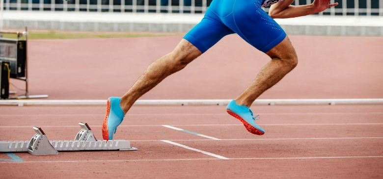 waist down view of man sprinting from blocks wearing compression shorts