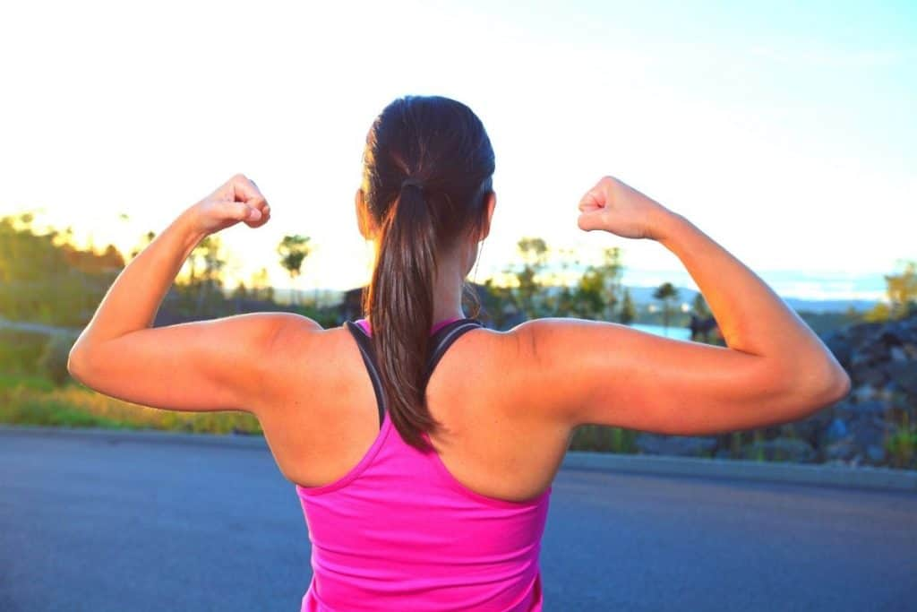 girl showing arm and upper back muscles during a walk