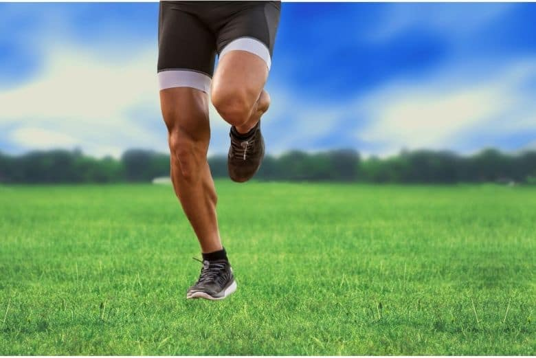 Lower region of man running in a field with compression pants