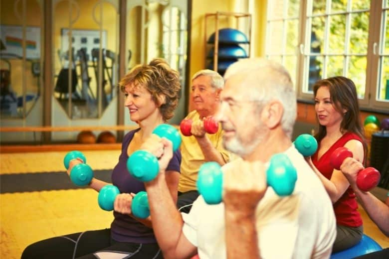 one of the best exercises for women over 50, dumbbell exercises in a class