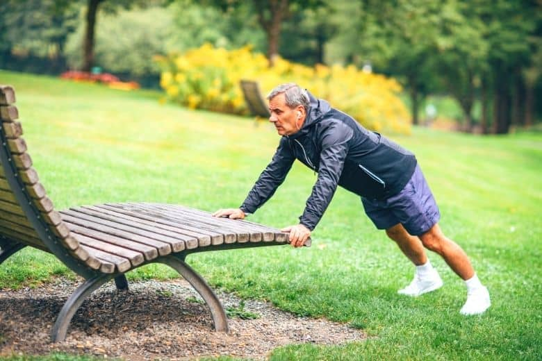 Older man outside exercising using a bench